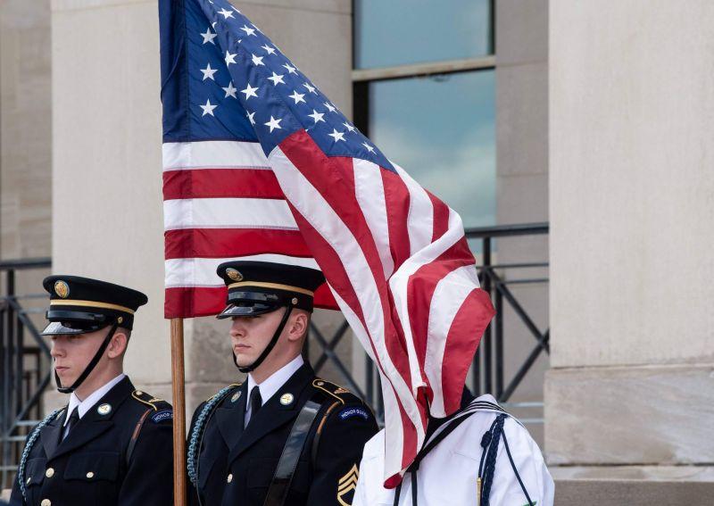 Un membre de la garde d'honneur a le visage recouvert par le drapeau américain, le 10 mai 2019 au Pentagone. Photo AFP / NICHOLAS KAMM