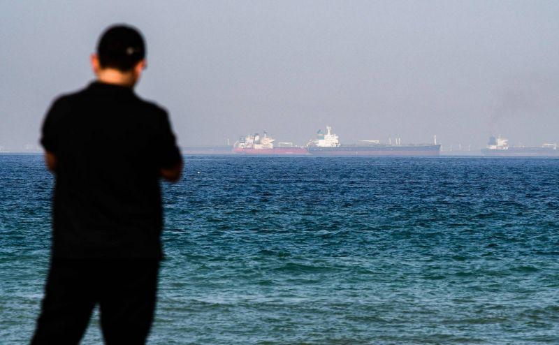 Un homme se tient sur la côte, alors qu'au loin des pétroliers naviguent dans le golfe d'Oman, le 15 juin 2019, au large de l'émirat de Fujeirah. Photo AFP/Giuseppe Cacace