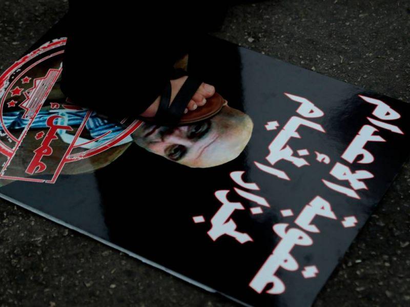 Une femme piétinant la photo de l'ex-chef militaire de l'Armée du Liban-Sud, Amer Fakhoury, lors d'un sit-in devant le Palais de justice de Beyrouth, le 12 septembre 2019. AFP / ANWAR AMRO