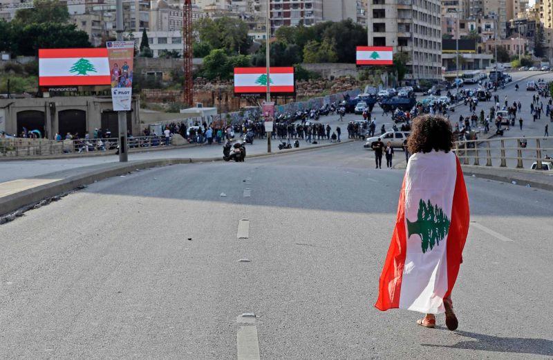 Une femme, le drapeau libanais sur les épaules, marche sur le pont du Ring, à Beyrouth, bloqué par les forces de sécurité qui tentaient d'empêcher les casseurs d'accéder au centre-ville, le 29 octobre 2019.  AFP / JOSEPH EID