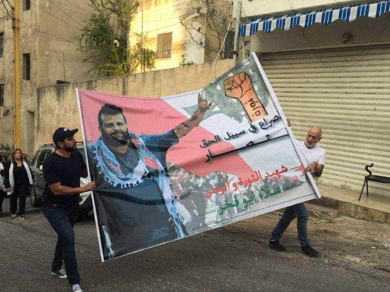 À Choueifate, des hommes portent un portrait géant de Ala' Abou Fakhr.