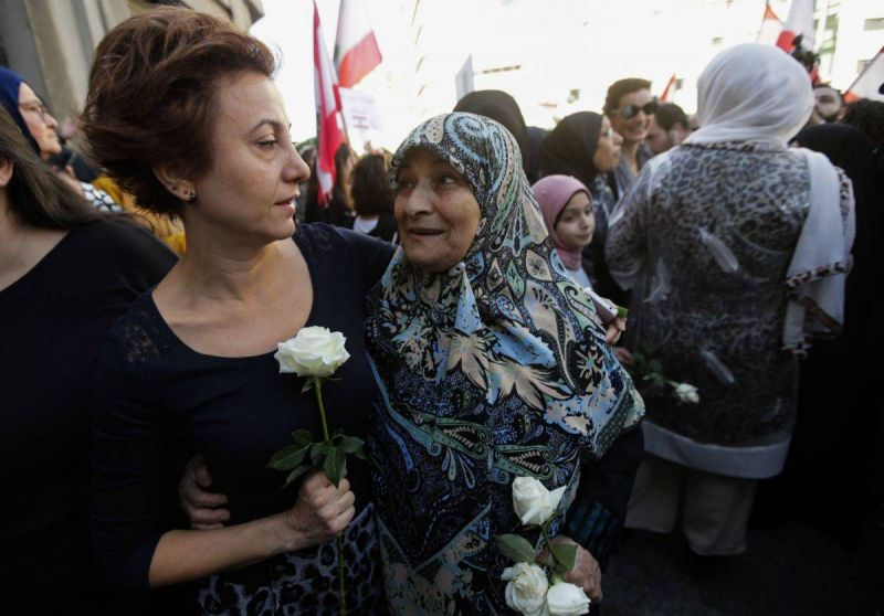 Two Lebanese women, one from the predominantly Muslim neighborhood of Khandak el-Ghamik, and the other from the Christian neighborhood of Tabaris, during a protest against violence and for national unity in Beirut on November 30, 2019. Photo AFP / ANWAR AMRO