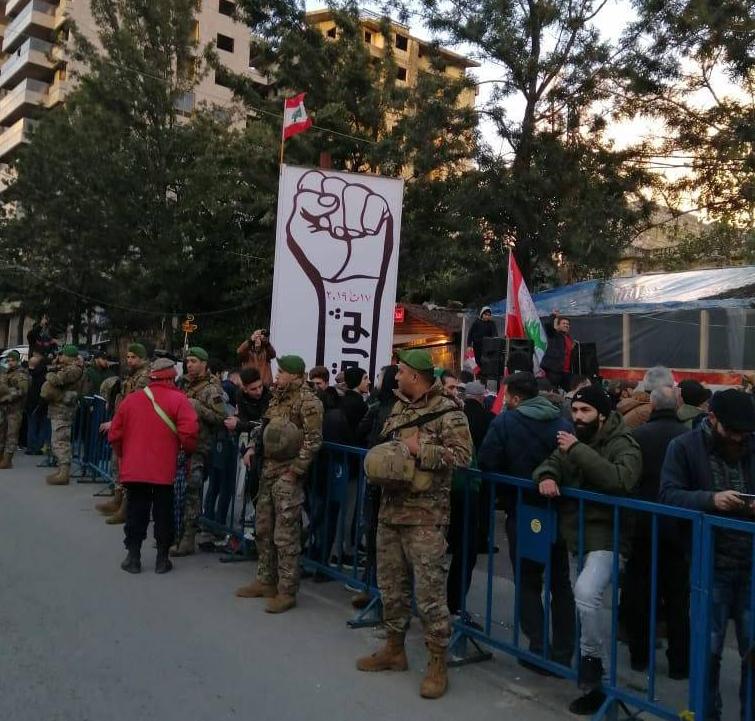 Des militaires protégeant les manifestants pacifiques vendredi à Nabatiyé, devant le «poing de la révolution» qu'ils venaient d'installer. Quelques heures plus tard, le poing sera incendié. Les contestataires verront dans cet acte l'empreinte des partisans d'Amal. Photo Badia Fahs